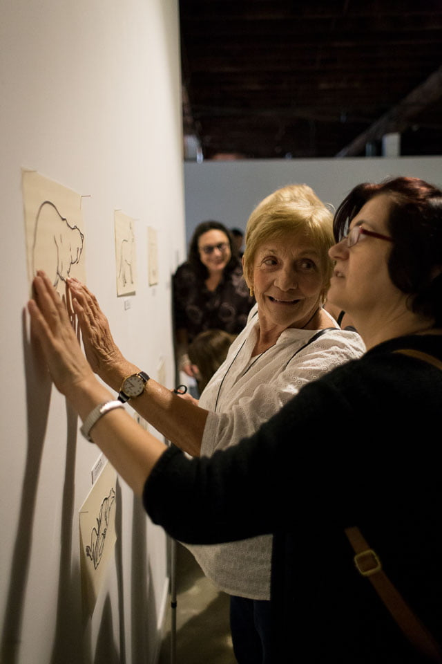 Two ladies touch the tactile drawing on a wall, one is wearing black and one is wearing white. They are smiling