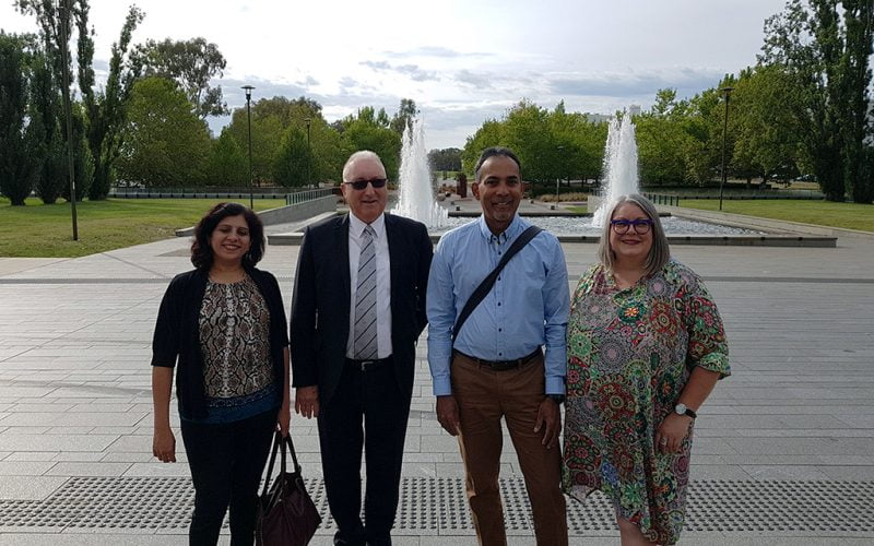 Four delegates outside in front of the fountains. Left to right: Sonali Marathe Royal Institute for Deaf and Blind Children, Tony Starky of Royal Society of the Blind, Dinesh Burah VisAbility team member, and Anthea Taylor Vision Australia.