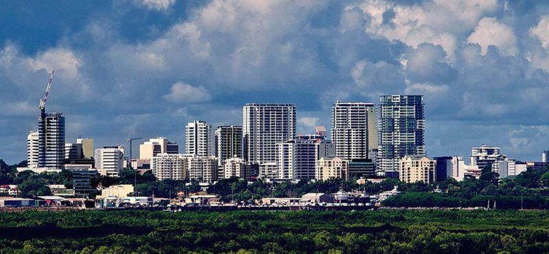 Image of the Darwin city skyline with blue, cloudy skies and green dense forest in the foreground