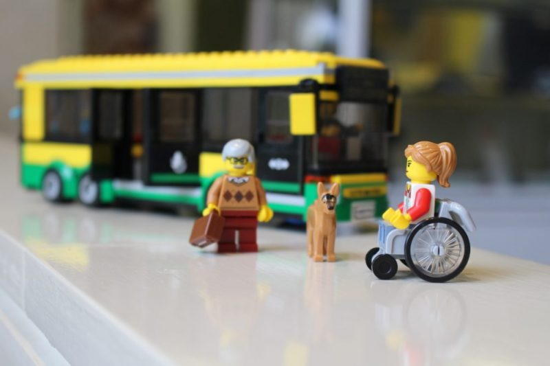 Image of the first LEGO set that includes people with a disability. Pictured is a LEGO bus, a man, a dog and a women in a wheel chair.