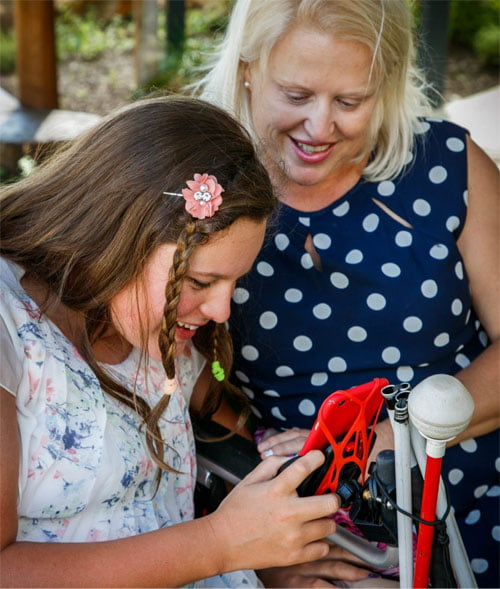 A young girl and her Mother look closely at a mobile phone. The girl is accessing a digital book