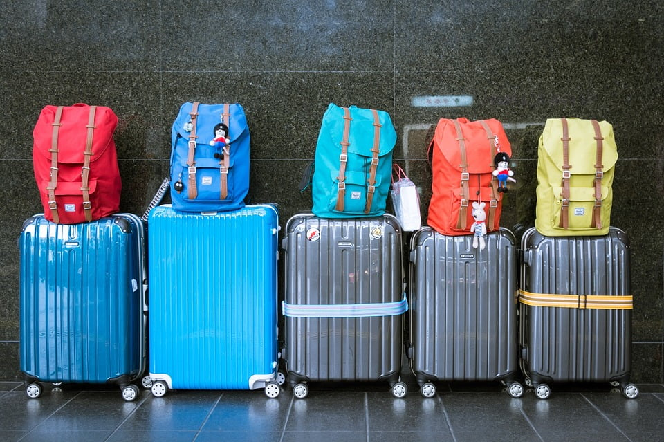 Image of a set of five suitcases with backpacks on top