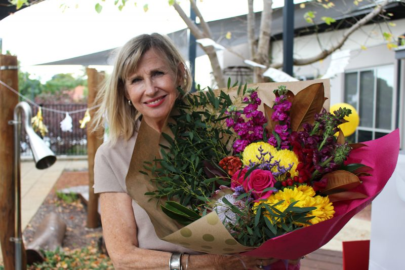 Louise Snowball at her Retirement Party with a bunch of flowers