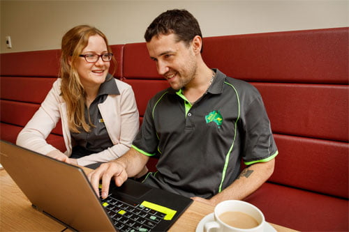 Image of a man working at a laptop with a cup of tea, as team member Sinead looks on.
