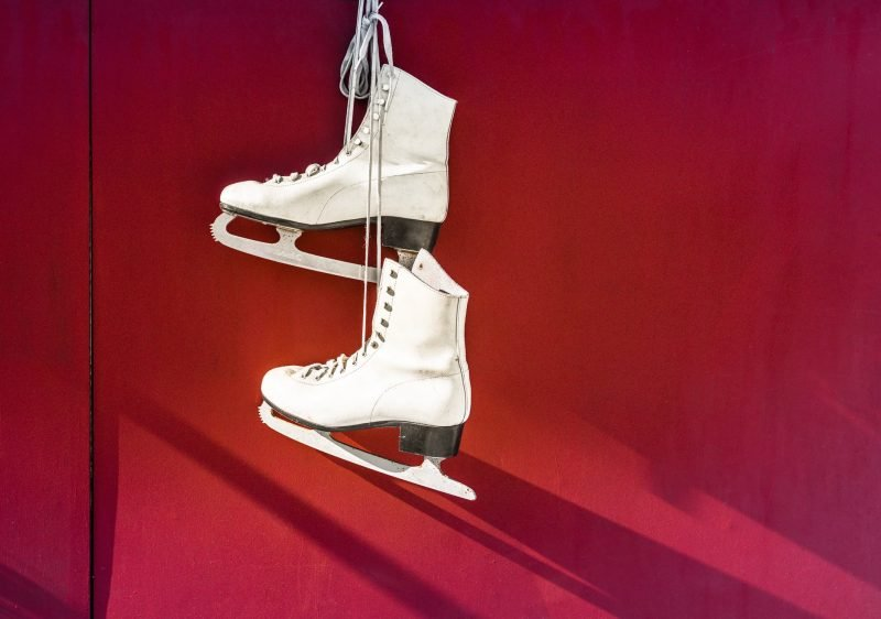 Two white ice skates on a red background