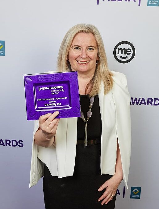 Image of Dr Clare Allen, VisAbility's Chief Executive Officer, holding the 2018 Outstanding Organisation Award