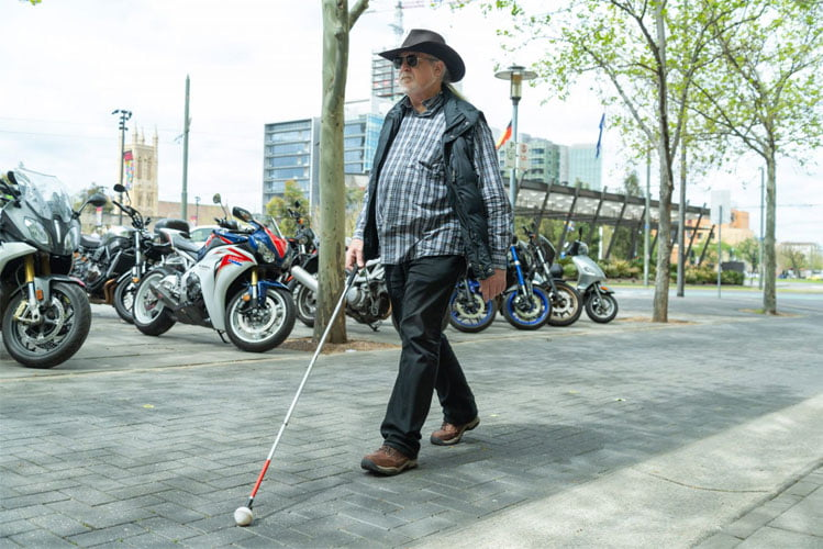 Image of a man walking down the street with his white cane
