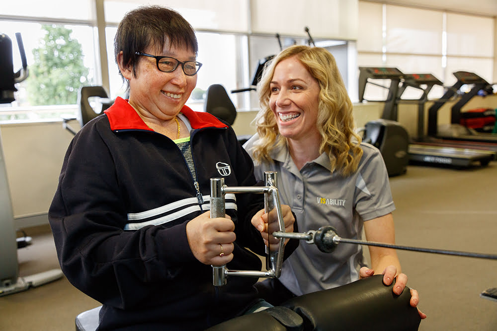 Image of Felicity, Exercise Physiologist, assisting a client during a session in the gym