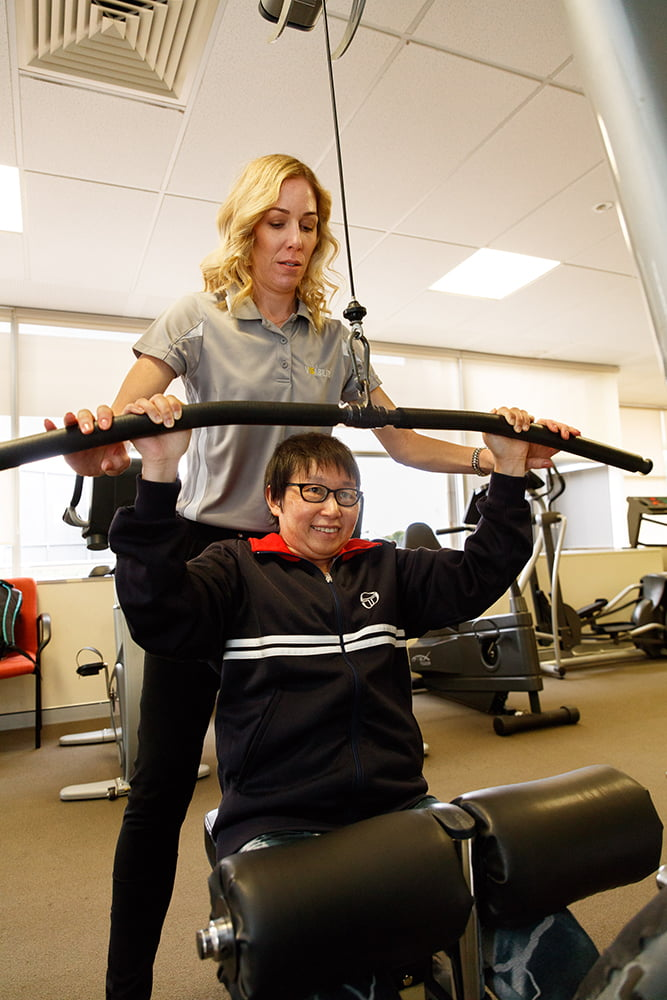 Image of Felicity, Exercise Physiologist, assisting a client during a session in the gym. Felicity helps a client with weight training.