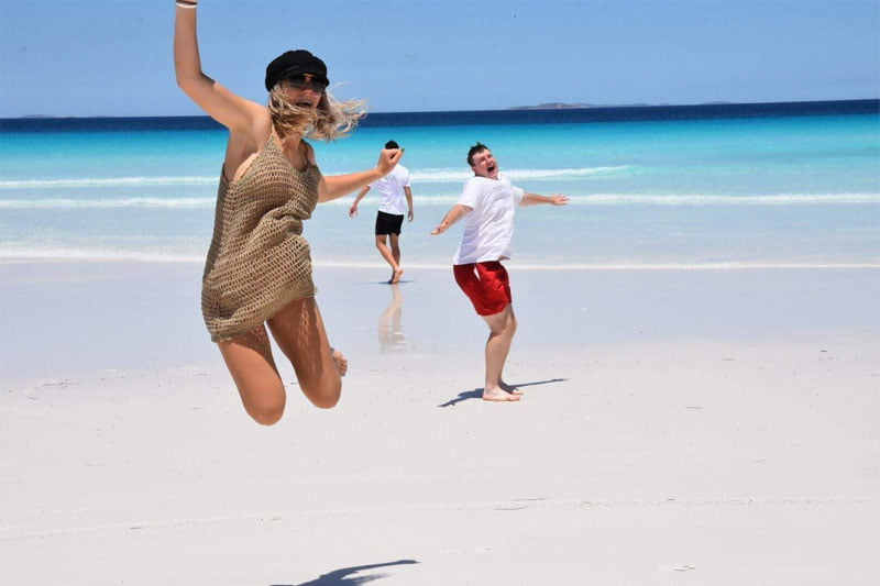 Image shows Georgie jumping for joy on a beach, with two of her friends in the background