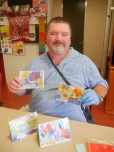 Image shows Keith Ryniker holding up some of the creative cards which he has made