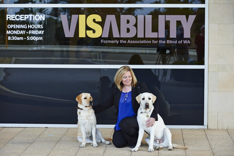 Image shows Dr Clare Allen with two of our Guide Dogs outside VisAbility in Victoria Park