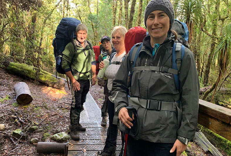 Image of happy hikers on a trail in the forest.