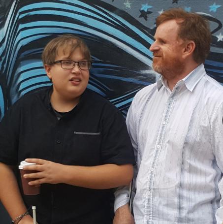 Harrison stands alongside Ryan against a muralled wall