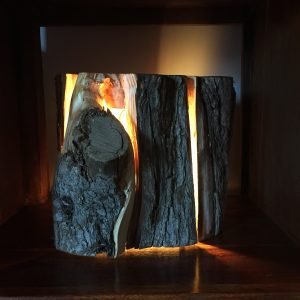 Cracked log lamp with light beaming through the cracks