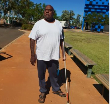 David walking along a road with his walking cane