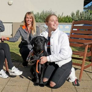 Tegan sits with a Guide Dog in its harness
