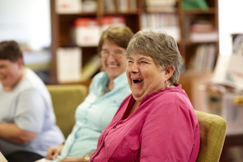 Woman sitting in chair laughing during a skills workshop, two other people looking on