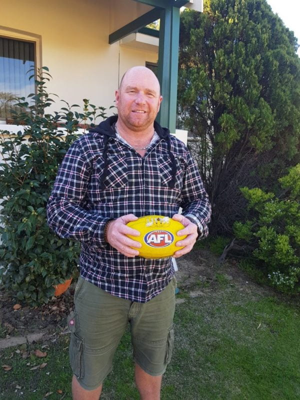 Todd holding yellow AFL ball