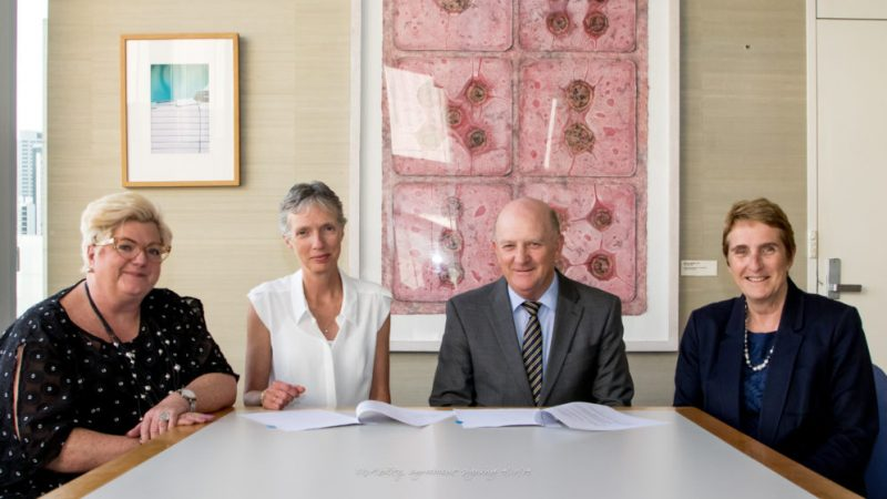 Four executives sit around a table for the formal signing.