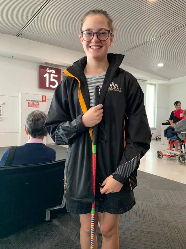 Caitlin Hannen-Williams with her cane at an airport