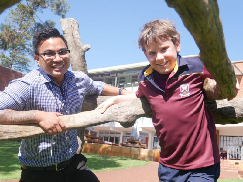 VisAbility occupational therapist Jeru Lopez stands next to Harry Nicholls in the open play area outside Scotch College.