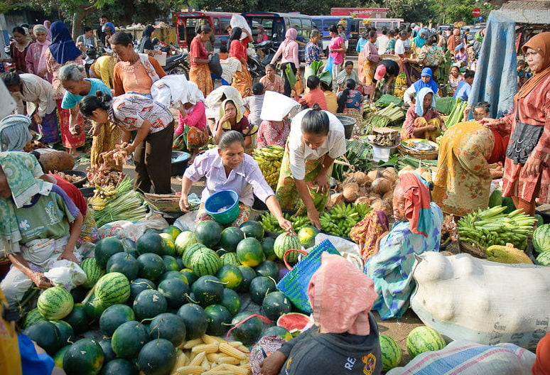 Image shows a busy Indonesian market with people buying fruit and vegetables