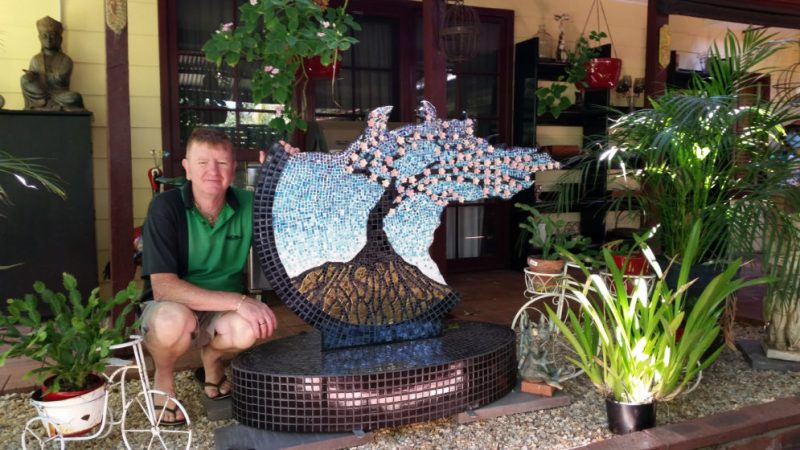 Graeme's partner Michael crouches next to the sculpture which is on their patio