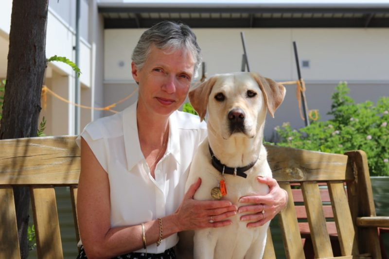 CEO Elizabeth Barnes seated on a bench with a Labrador Guide Dog.