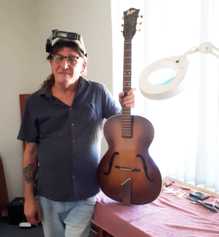 Les stands next to one of his guitars which he has built
