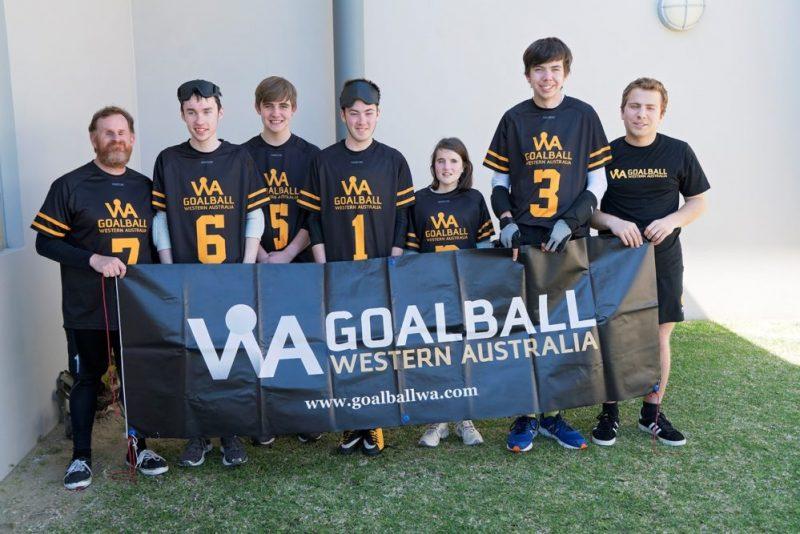 Team members of Goalball hold banner which reads Goalball Western Australia