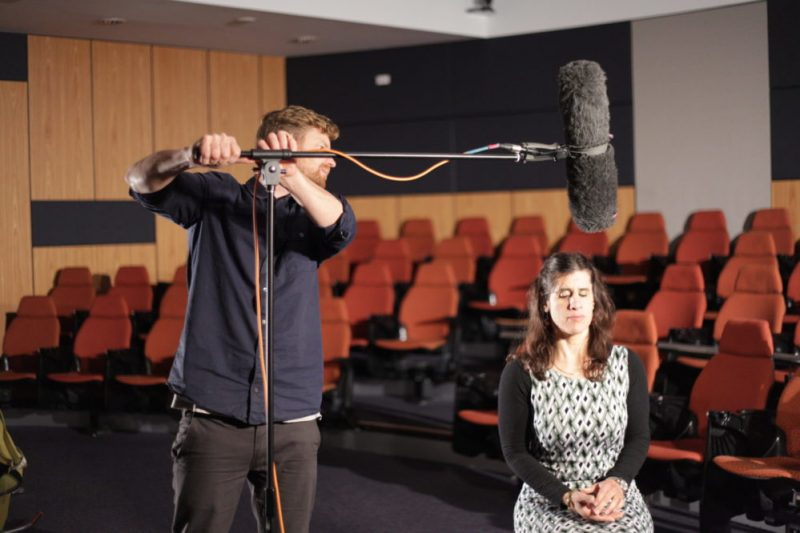Zel Iscel is seated with sound man adjusting a boom microphone above her head.