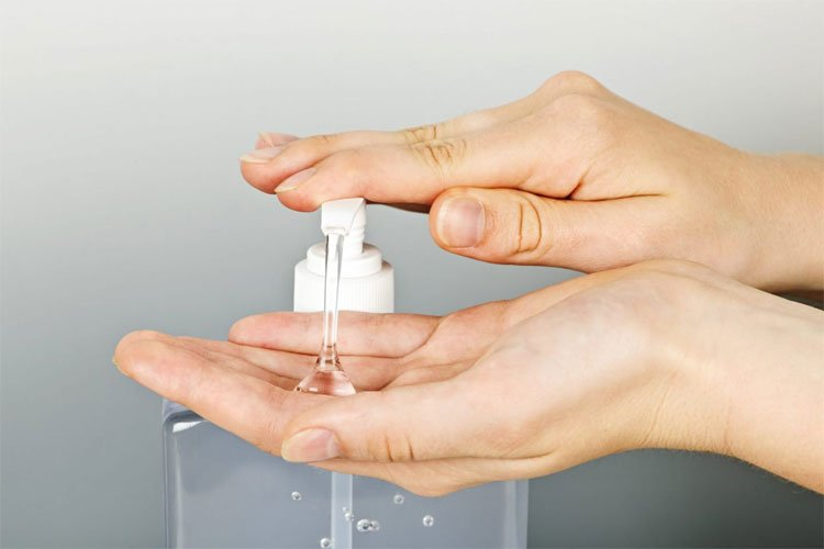 A person's hands pressing down on a hand sanitizer unit