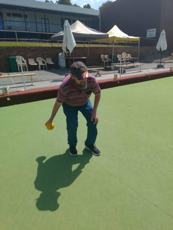 Phil is on a bowling lawn playing bowls