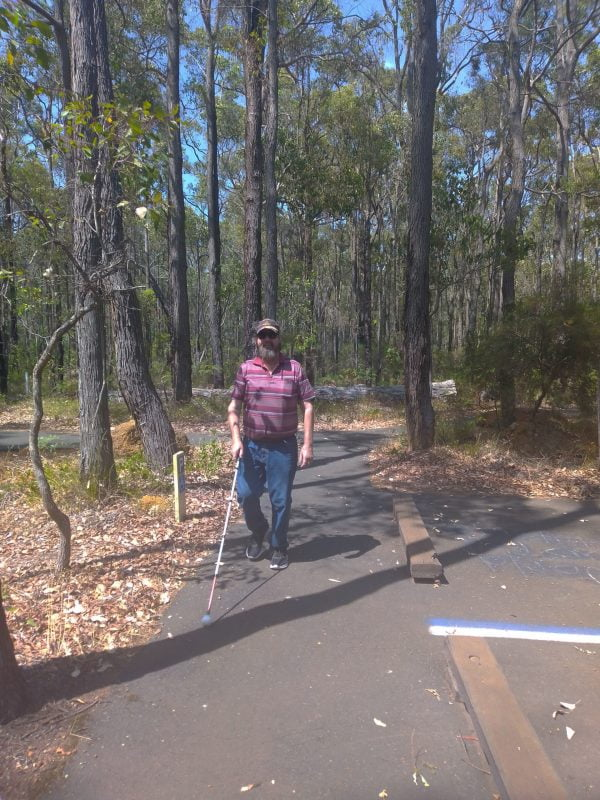 Phil walks along a forested area holding his white cane