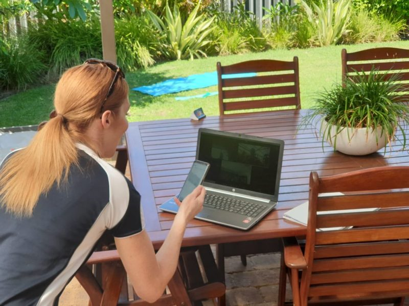 Felicity sits at a garden table, in front of laptop with a phone in her hand