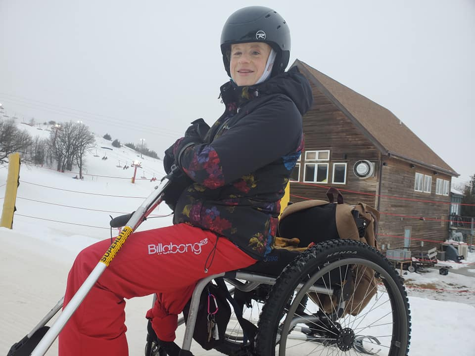 Kylie on slope in her all terrain wheelchair smiling holding outriggers