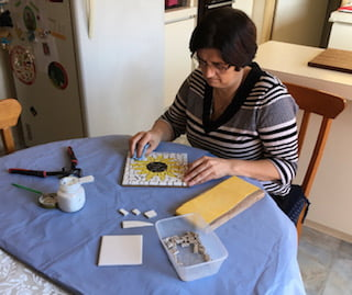 Tiziana who usually works in the Community Activity Centre at VisAbility carries out a mosaic on her table