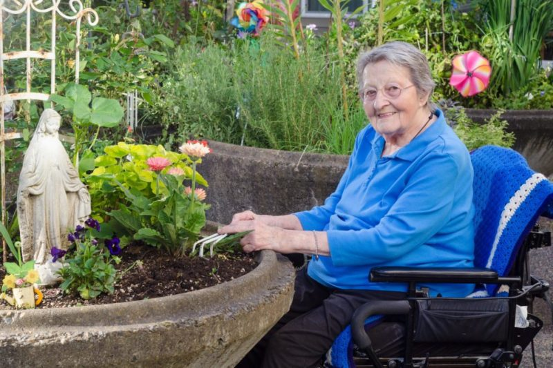 Lady in wheelchair doing gardening by a pot plant