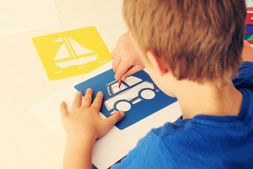Picture of child tracing a car using a stencil