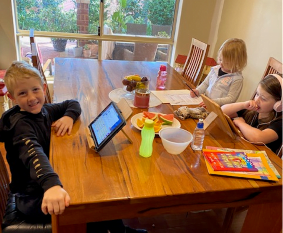 Three children sit around a table with fruit in the middle of the bowl during COVID-19 isolation