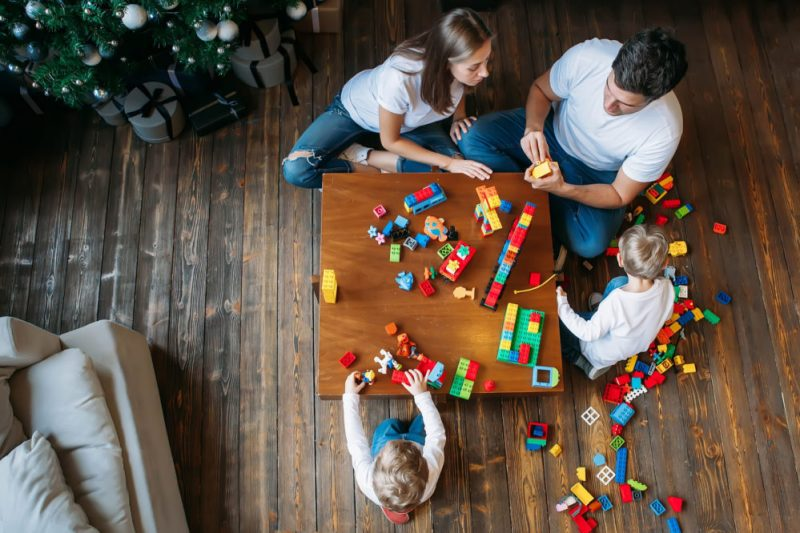 Ariel shot of two children and their parents playing with Lego on a wooden table.