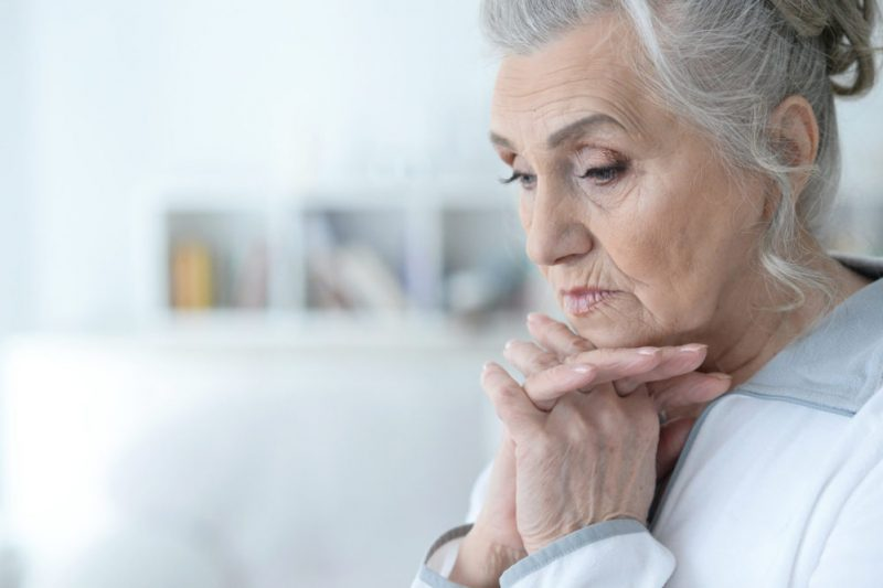 Older woman looks pensive and slightly worried.
