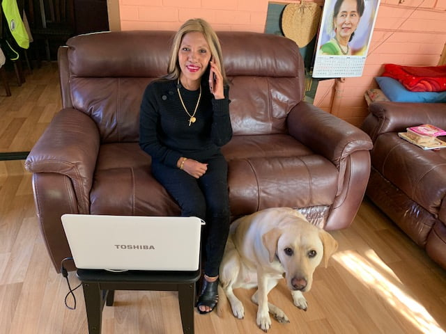 Jacqui sits on a settee in the lounge of her own home with her Guide Dog Della in front of her