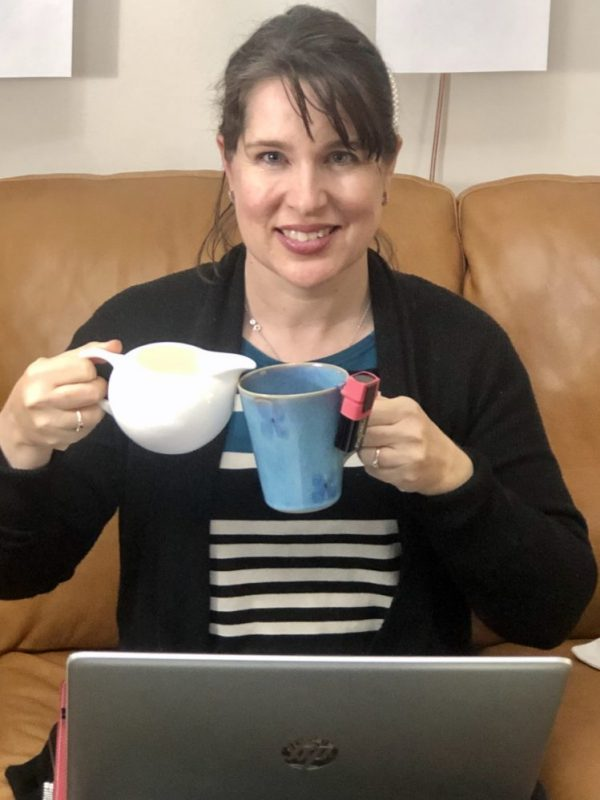 Rebecca sits in front of a laptop with a jar in one hand and cup of coffee in the other with spill device attached to it
