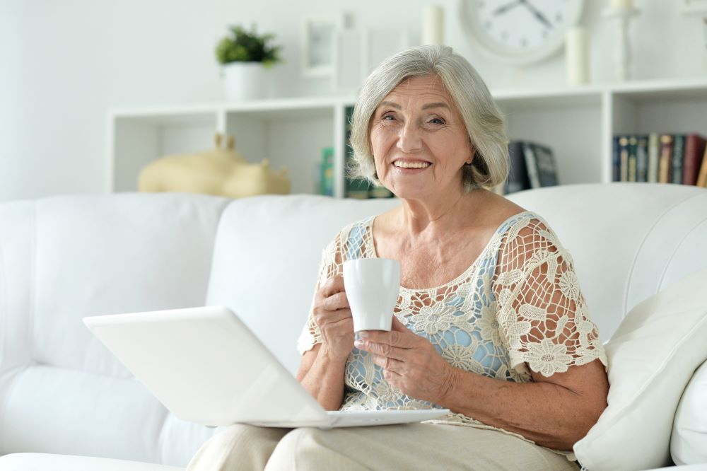 Woman sitting on her couch with a cup of tea with her laptop on her lap