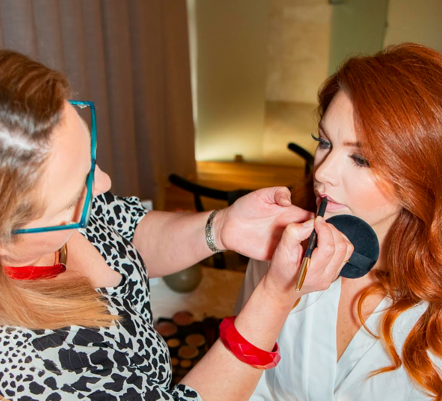 Vanessa applies make-up with a  brush to a lady's lips