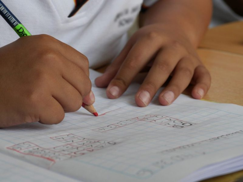 Image is close up of child's hands doing maths work in a school