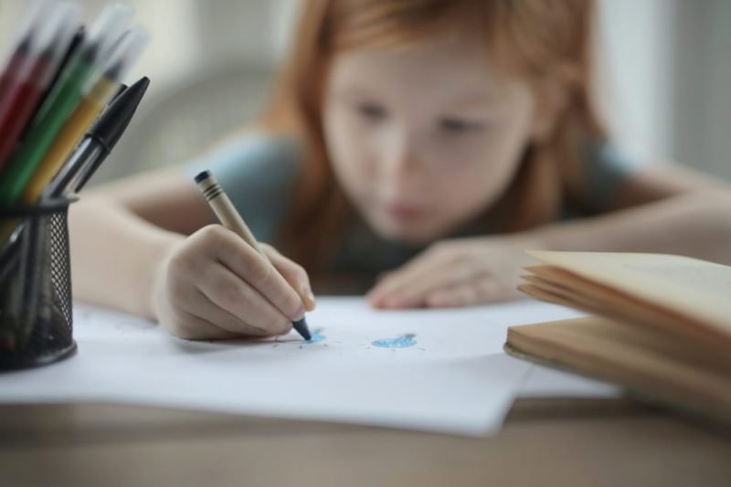 Image shows child colouring at table in school environment