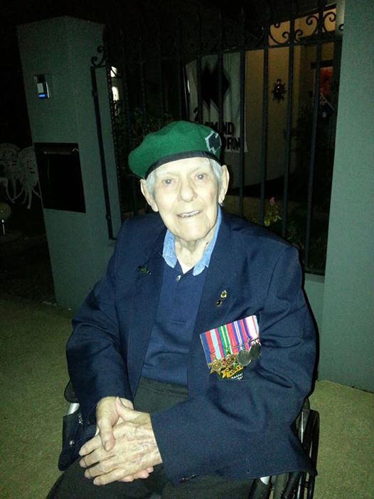 War hero Harold Durant, smiling sits in his wheelchair with his Commando Beret, and medals on his suit jacket.